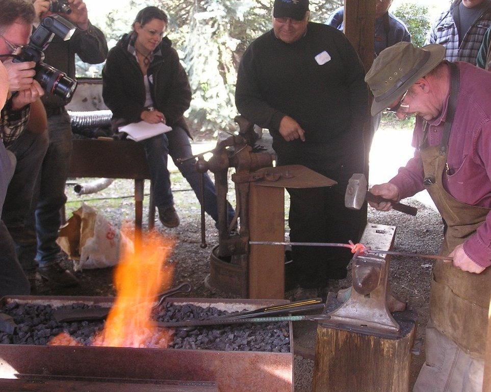 folks watch a blacksmith at work